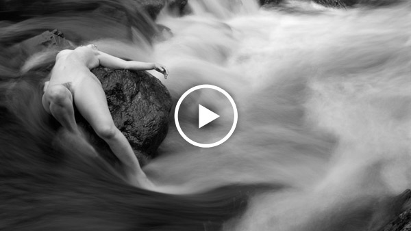 nude art model on rocks in a river